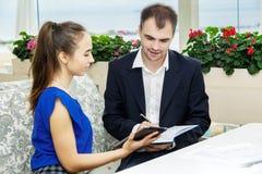 Affärsmannen och hans sekreterare som tillsammans arbetar dagboken gör mananmärkningar Arkivbild