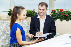 Affärsmannen och hans sekreterare som tillsammans arbetar dagboken gör mananmärkningar Royaltyfri Foto