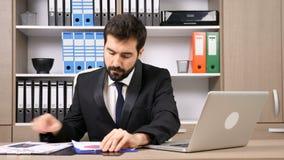 Affärsmannen på hans skrivbord som arbetar på datoren och någon, skyler över brister lager videofilmer
