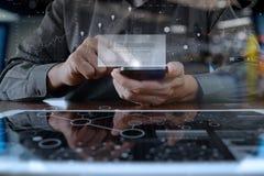 Affärsmannen räcker genom att använda den digitala pro-minnestavlan och ilar telefonen Arkivbilder