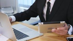Affärsmannen räcker maskinskrivning på bärbar datordatoren på trätabellen och gör några anmärkningar långsam rörelse arkivfilmer