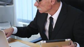 Affärsmannen räcker maskinskrivning på bärbar datordatoren på trätabellen och gör några anmärkningar långsam rörelse lager videofilmer