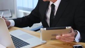 Affärsmannen räcker maskinskrivning på bärbar datordatoren på trätabellen och gör några anmärkningar långsam rörelse stock video