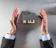 Affärsmannen räcker uppvisning av ett hus för att köpa, ovanför sikt Arkivbild
