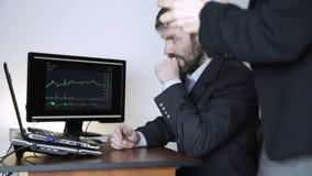 Affärsmannen råder klienten på videokommunikationen för arbete på en crypto börs hållande ögonen på diagram för valutautbyte på stock video