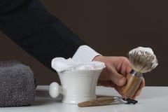 Affärsmannen rymmer att raka utrustning i hans hand royaltyfri foto
