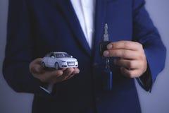 Affärsmannen rymmer bilen och tangenter royaltyfria foton