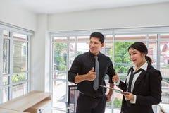 Affärsmannen rymmer en tumme Man av affärshålltummen upp Affärskvinnainnehavskrivplatta med arket av papper och pennan Man och royaltyfria foton