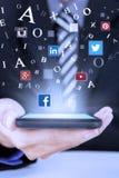 Affärsmannen rymmer smartphonen med sociala massmediasymboler royaltyfria foton