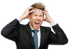 Affärsmannen sätter händer på det spruckna huvudet och ropar Royaltyfri Foto