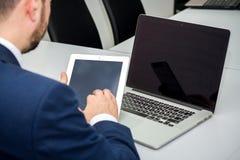 Affärsmannen söker efter användbar information på planchetten royaltyfria bilder
