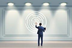 Affärsmannen söker efter vägar att fly från labyrintlabyrint royaltyfria foton