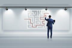 Affärsmannen söker efter vägar att fly från labyrintlabyrint royaltyfri foto