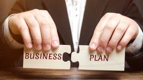 Affärsmannen samlar pussel med ordaffärsplanet Program för affärsoperationer Organisation och ledning av processar arkivbild