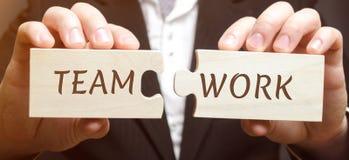 Affärsmannen samlar träpussel med ordteamworken Gemensam prestation av ett gemensamt mål Hög effektivitet och kapacitet arkivfoto