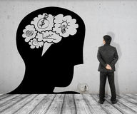 Affärsmannen ser begreppsbilden av bubblasamtalhjärnan i huvud på vit tegelsten däcka och betongväggen royaltyfri bild