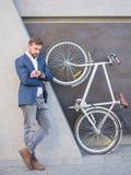 Affärsmannen ser hans klocka, bredvid en cykel lyfts på hans bakre ben Royaltyfria Foton