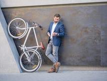 Affärsmannen ser hans telefon, bredvid en cykel lyfts på hans bakre ben Arkivfoto