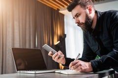 Affärsmannen ser skärmen av smartphonen, läser meddelandet, medan göra anmärkningen i notepad Entreprenören analyserar informatio Royaltyfri Bild