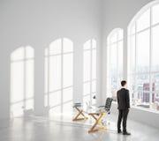 Affärsmannen ser ut fönstret i inre rum för vind med glas Royaltyfri Fotografi