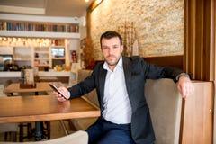Affärsmannen sitter i restaurang Arkivbilder