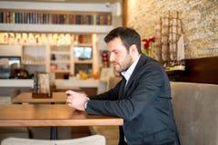 Affärsmannen sitter i restaurang och använder hans telefon Royaltyfri Fotografi