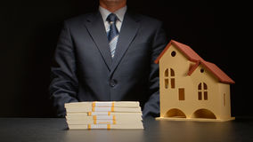 Affärsmannen sitter nära en pengarbunt och en husmodell på en tabell Arkivfoton