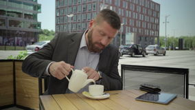 Affärsmannen sitter ner på tabellen och häller te in i koppen, steadicam lager videofilmer