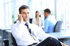 Affärsmannen sitter på hans skrivbord, medan tala på mobil i regeringsställning Arkivfoto