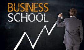 Affärsmannen skriver affärsskolan på svart tavlabegrepp Royaltyfri Bild