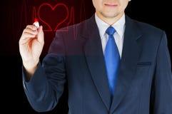 Affärsmannen skriver den röda hjärtalinjen över svart bakgrund arkivbild