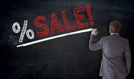 Affärsmannen skriver försäljning på svart tavlabegrepp Royaltyfria Bilder