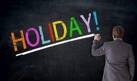 Affärsmannen skriver ferie på svart tavlabegrepp Arkivfoton