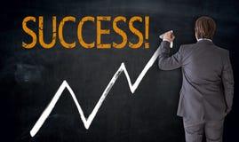 Affärsmannen skriver framgång på svart tavlabegrepp Arkivfoto