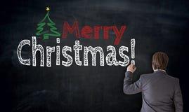 Affärsmannen skriver glad jul på svart tavlabegrepp Arkivfoto
