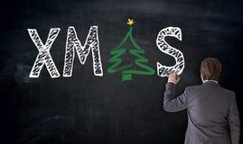 Affärsmannen skriver XMAS på svart tavlabegrepp Arkivbilder