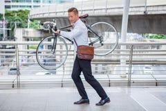 affärsmannen skynda sig upp och bära hans cykel för att hålla ögonen på klockan som kontrollerar tid till sent på stadsgator för  royaltyfria bilder