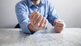 Affärsmannen slår tabellen med hans nävar Begrepp av ilska arkivfoto