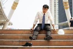 Affärsmannen, som är trött eller stressad, sitter på trappan Arkivbilder