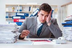 Affärsmannen som är upptagen med mycket skrivbordsarbete royaltyfria bilder