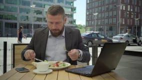 Affärsmannen som äter lunch, är i brådska och går bort, steadicam stock video