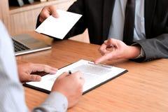 Affärsmannen som överför avsägelsebrevet till framstickandet, och hållande material avgår för att trycka ned eller den bärande ka arkivbild