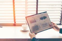 Affärsmannen som analyserar investering, kartlägger i arbetsutrymmet Arkivfoton