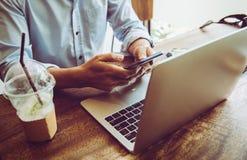 Affärsmannen som använder mobilen, och bärbara datorn finner ett jobb i coffee shop royaltyfria bilder