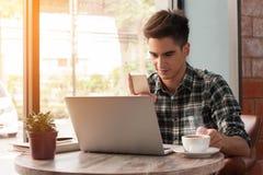 Affärsmannen som använder smartphone- och bärbar datorhandstil på minnestavlan uppvaktar på Arkivbild