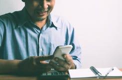 Affärsmannen som använder smartphonen och, tycker om med begrepp är för busin fotografering för bildbyråer