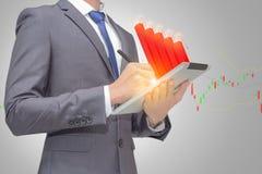 Affärsmannen som använder touchpaden, minnestavla för att hämta och analysera data med den röda pinnen, graph indikatorn Arkivbilder