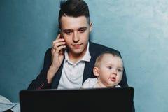 Affärsmannen som arbetar att hålla ögonen på, behandla som ett barn hemma dottern royaltyfri fotografi
