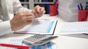 Affärsmannen som arbetar och beräknar, läser och skriver rapporter Kontorsanställd, tabellcloseup Conce för finansiell redovisnin lager videofilmer