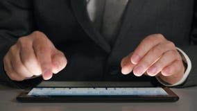 Affärsmannen som arbetar på en minnestavla, analyserar graferna och tabellerna, handcloseup